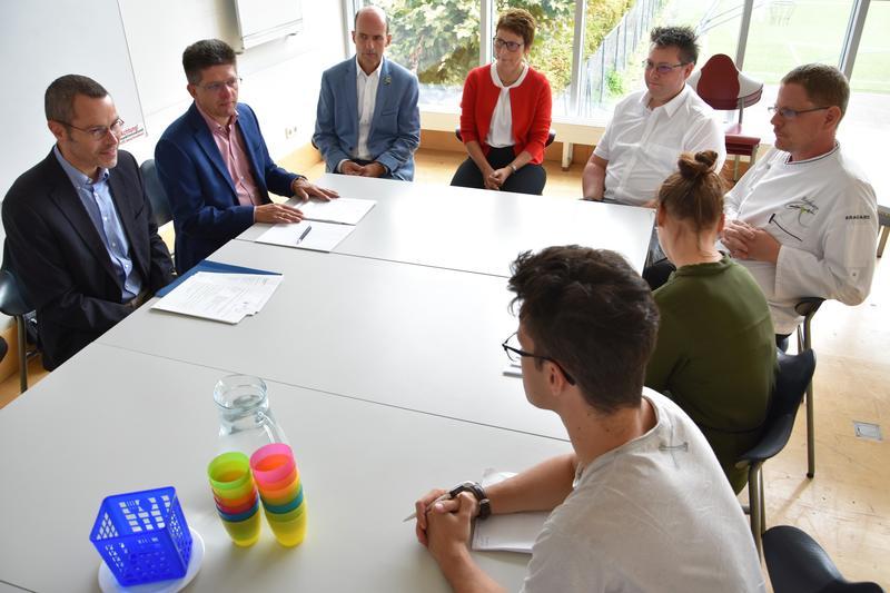 Einmal zurück in die Schulzeit versetzt fühlten sich Bürgermeister Dr. Maximilian Ingenthron, Schulamtsleiter Ralf Müller, Caterer René Rebmann und Vertreterinnen und Vertreter der Schule sowie der Presse beim Vor-Ort-Termin in der Mensa des Otto-Hahn-Gymnasiums.