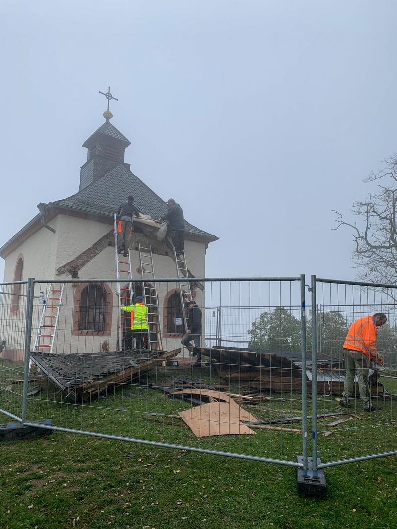 Freiwillige Helferinnen und Helfer, darunter die Einheit Arzheim der Freiwilligen Feuerwehr Landau, helfen bei der Sicherung des Dachs der Kapelle auf der Kleinen Kalmit.